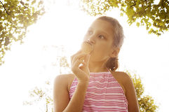 女孩坐草在公园。 库存照片