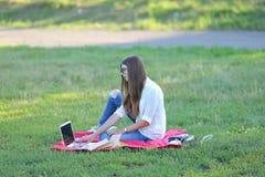 女孩坐草在公园和工作在膝上型计算机 库存照片