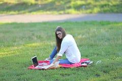 女孩坐草在公园和工作在膝上型计算机 库存图片