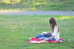 女孩坐草在公园工作在膝上型计算机和吃快餐 免版税库存图片