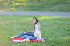 女孩坐草在公园工作在膝上型计算机和吃快餐 库存照片