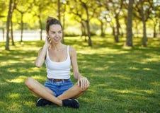 女孩坐草在公园 库存照片