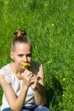 女孩坐草用蒲公英在手上 免版税图库摄影