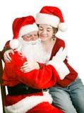 女孩坐获得拥抱的圣诞老人膝部 免版税库存照片