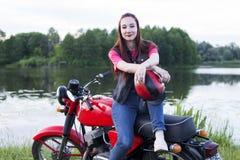 女孩坐葡萄酒摩托车户外 库存照片