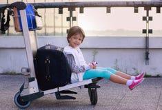 女孩坐行李台车等待的飞行乘飞机 Girk,孩子在机场 免版税库存照片