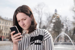 女孩坐街道并且给某人写sms 库存图片