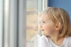 女孩坐视窗 免版税库存图片
