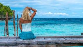 女孩坐调查蓝色海洋, Gam海岛,西部Papuan,王侯Ampat,印度尼西亚的居住的时期的木码头 免版税库存照片