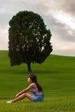 女孩坐这一树小山,看 免版税图库摄影