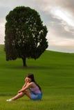 女孩坐这一树小山,看 免版税库存图片