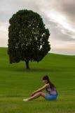 女孩坐这一树小山 库存照片