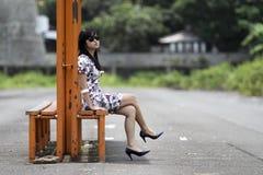 女孩坐铁长凳 库存照片