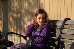 女孩坐长凳在下午阳光下 免版税库存照片