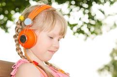 女孩坐长凳在公园和听的语言音频cours 图库摄影