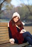 女孩坐长凳在公园 免版税库存照片