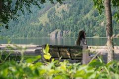 女孩坐长凳在河附近 库存图片