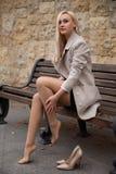 女孩坐长凳在秋天公园 免版税库存图片