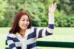 女孩坐长凳,挥动的手 库存照片