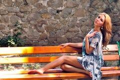 女孩坐长凳 免版税库存照片