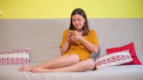 女孩坐长沙发使用一个手机 股票视频