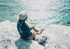 女孩坐陡峭的海岸 库存图片