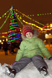 女孩坐雪和笑 库存图片