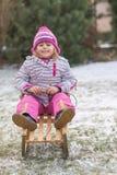 女孩坐雪撬 库存图片