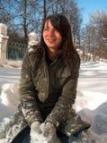 女孩坐雪 免版税库存图片
