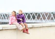 女孩坐水坝栏杆  免版税库存照片