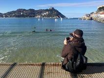 女孩坐Donostia圣塞巴斯蒂安,巴斯克地区,城市,西班牙码头  La外耳全景海滩  免版税图库摄影