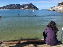 女孩坐Donostia圣塞巴斯蒂安,巴斯克地区,城市,西班牙码头  La外耳全景海滩  免版税库存图片