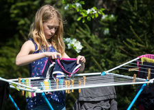 女孩垂悬的洗衣店在庭院里 免版税库存照片