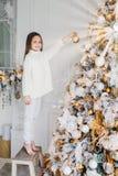 女孩垂直的画象在新年树附近站立,拿着装饰的新年球,装饰杉树,有愉快的expressi 免版税库存图片