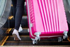 女孩培养在自动扶梯的一个桃红色手提箱 库存图片