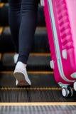 女孩培养在自动扶梯的一个桃红色手提箱 免版税库存图片