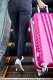 女孩培养在自动扶梯的一个桃红色手提箱 免版税库存照片