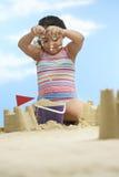 女孩大厦在海滩的沙子城堡 免版税库存图片
