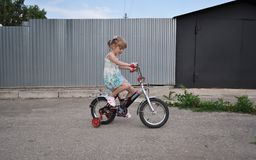 女孩大约五岁学会骑自行车 免版税库存图片