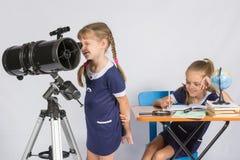 女孩天文学家通过望远镜的目镜和愉快地坐另一个的女孩看桌 库存照片