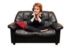 女孩头发的红色坐的沙发 库存照片