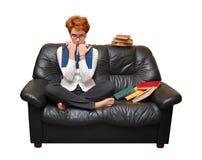 女孩头发的红色坐的沙发 免版税库存图片