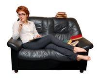 女孩头发的红色坐的沙发 免版税图库摄影