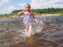 女孩奔跑在水中 免版税库存照片