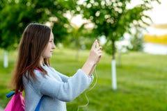 女孩女小学生少年 夏天本质上 在他的手上拿着在他的背包后的一个智能手机 在电话的照片 库存照片