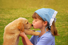 女孩她亲吻的小的小狗 免版税库存图片