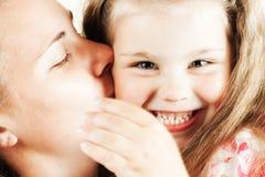 女孩她亲吻的母亲 免版税图库摄影
