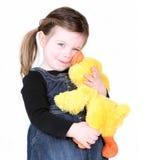 女孩她拥抱一点个被充塞的玩具 免版税图库摄影