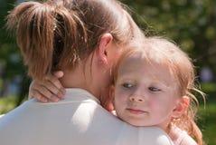 女孩她拥抱的小的母亲脖子s 免版税图库摄影