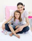 女孩她拥抱的母亲微笑 免版税库存图片